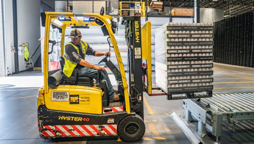 image of worker reversing forklift in warehouse