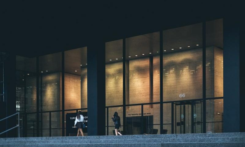 benefits of installing aluminium doors, two women walking past a huge glass building
