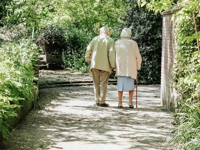 create a safe environment for the elderly, a senior couple walking on a road surrounded by trees