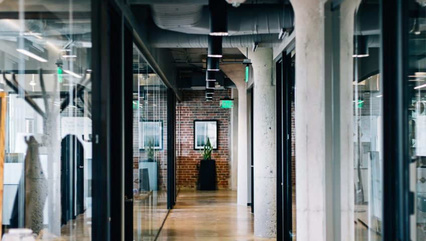 Robust office doors are a great idea to consider for office improvement; a wide aisle in an office with dark glass doors and brown marble flooring