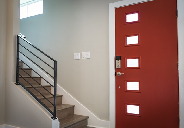 Aluminum Door Myths; A red coloured main door with heavy-duty security lock intalled beside a stairway.