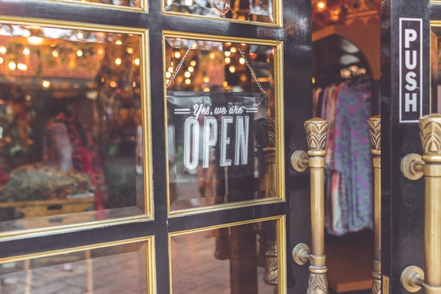 Common Commercial Doors For Business; A glass door opening to enter a retail store.